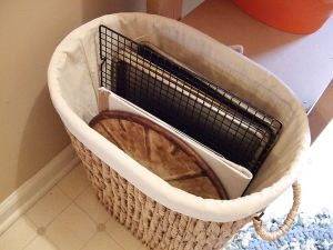 When you're short on storage for your baking pans a large decorative basket works great and looks nice.